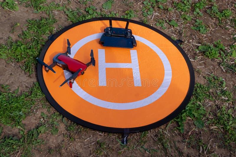 Hommel op de helihaven hommeltelefoon en controlebord op een oranje helihaven op het gras royalty-vrije stock afbeeldingen