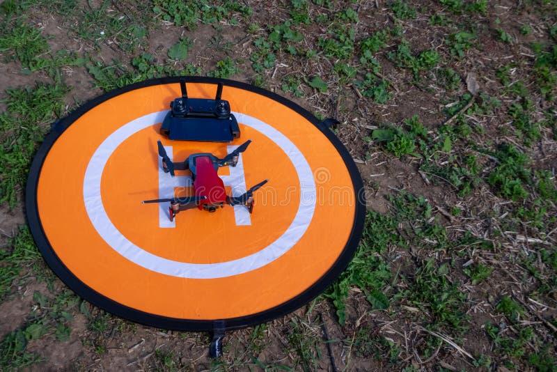 Hommel op de helihaven hommeltelefoon en controlebord op een oranje helihaven op het gras royalty-vrije stock afbeelding