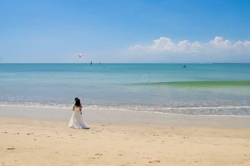 Hommel over het kussen van bruid en bruidegom op mooi strand, Bali stock afbeelding
