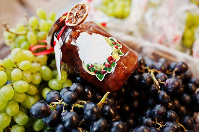 Hommemade jar with grapes on the shelf of a supermarket or grocery store.  stock photo