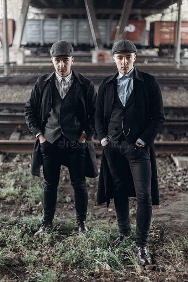 Hommes élégants de bandits, posant sur le fond du chemin de fer thème de l'Angleterre en 1920 s groupe sûr brutal à la mode m atm photos libres de droits