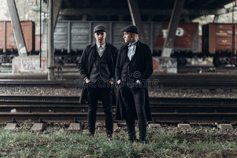 Hommes élégants de bandits, posant sur le fond du chemin de fer thème de l'Angleterre en 1920 s groupe sûr brutal à la mode m atm photo libre de droits
