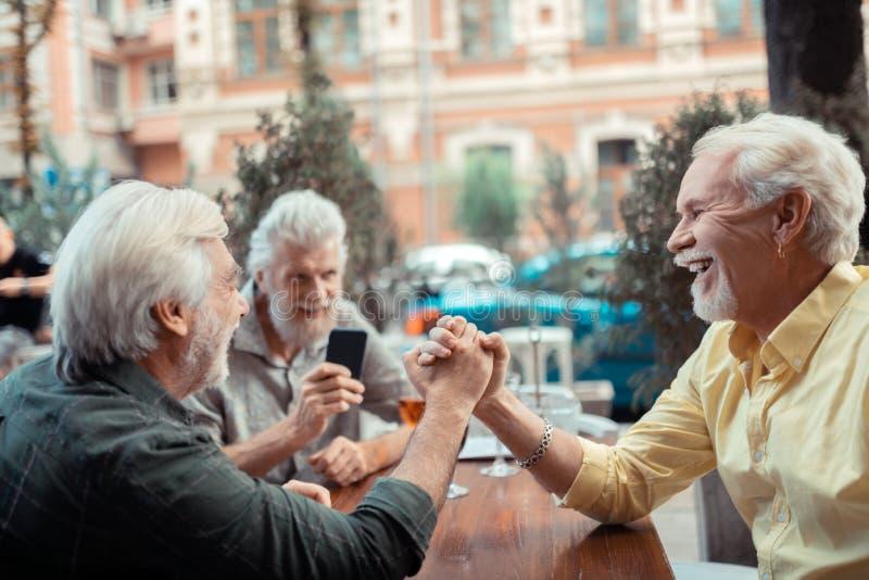 Hommes actifs aux cheveux gris gais riant le bras de fer de moment photos stock
