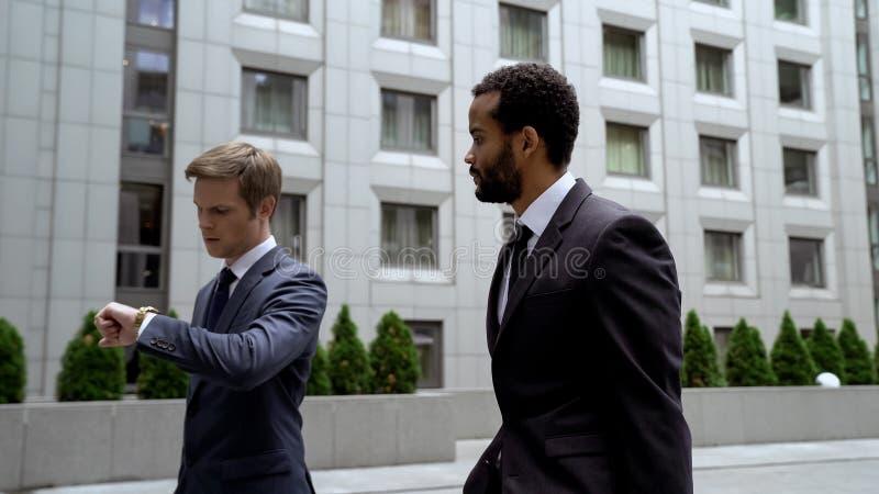 Hommes allant à la réunion d'affaires importante, regardant la montre, gestion du temps image libre de droits
