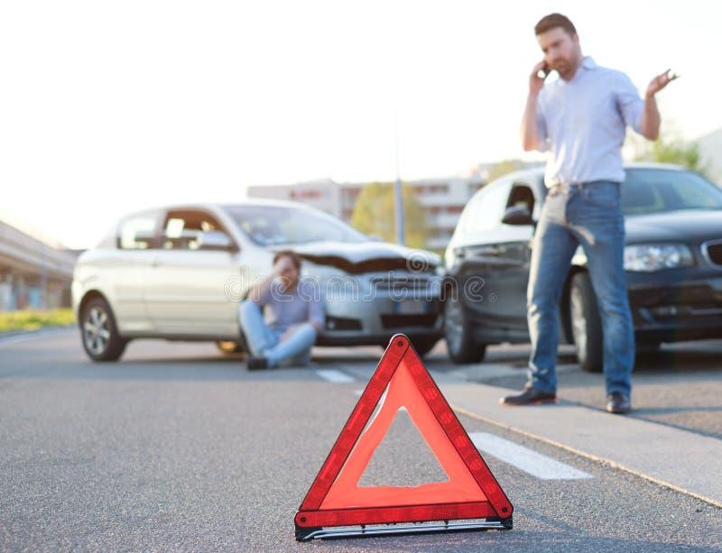 Hommes appelle des premiers secours après un mauvais accident de voiture sur la route image stock