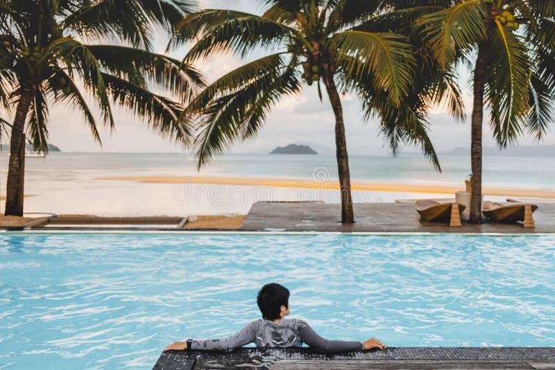 Hommes asiatiques détendant dans des vacances d'été de piscine sur la plage photos stock