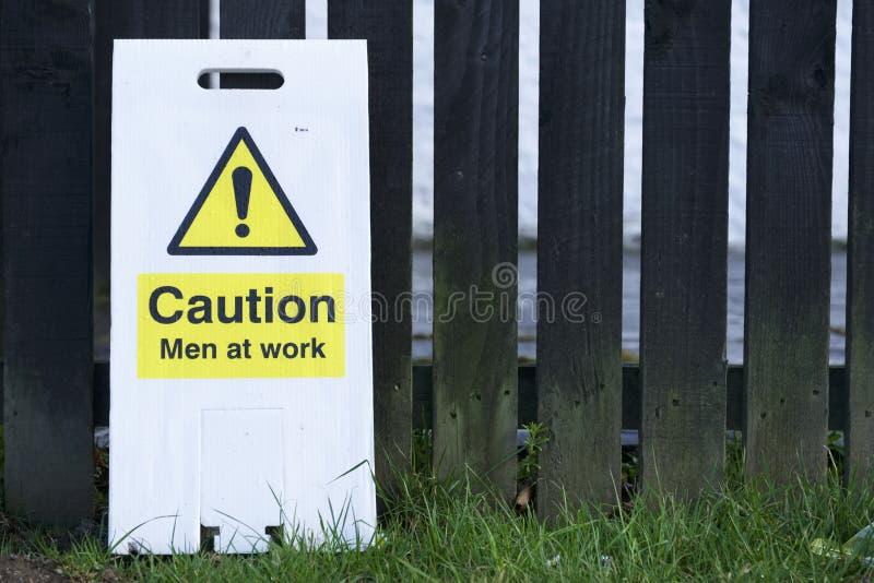 Hommes au signe d'attention de travail photos stock