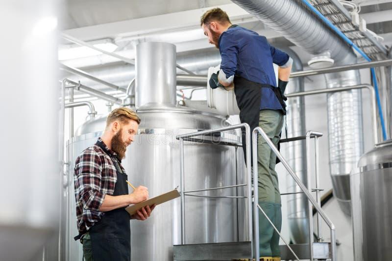 Hommes avec le presse-papiers à la bouilloire de brasserie ou à l'usine de bière photographie stock libre de droits