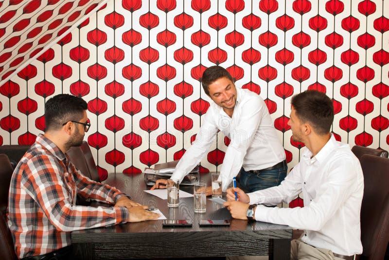 Hommes ayant la discussion heureuse lors de la réunion photographie stock libre de droits