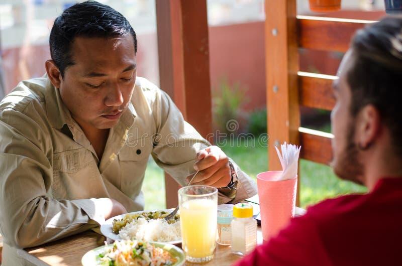Hommes beaux prenant le déjeuner dans un restaurant extérieur, causerie d'hommes photo libre de droits