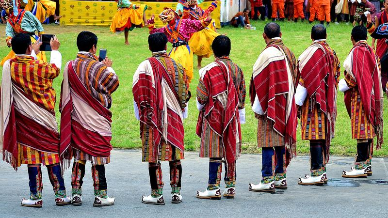 Hommes bhoutanais dans leur meilleur vêtement traditionnel étant témoin d'une danse spectaculaire et sacrée de masque photos stock