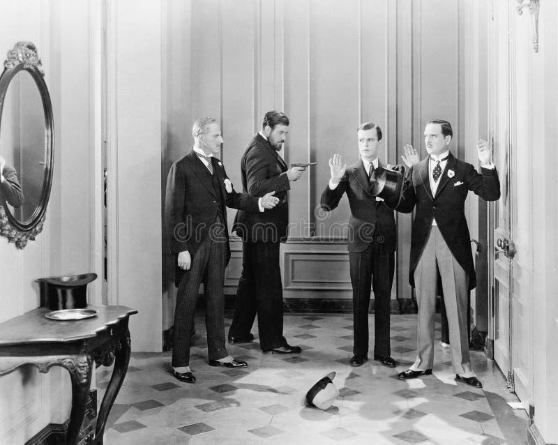 Hommes bien habillés étant supportés avec des armes à feu par deux autres hommes (toutes les personnes représentées ne sont pas p image stock