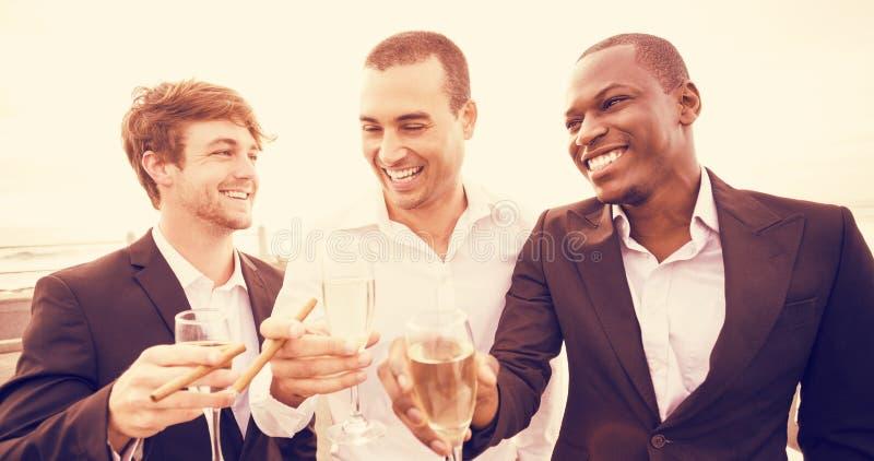 Hommes bien habillés buvant du champagne à côté de la limousine image stock