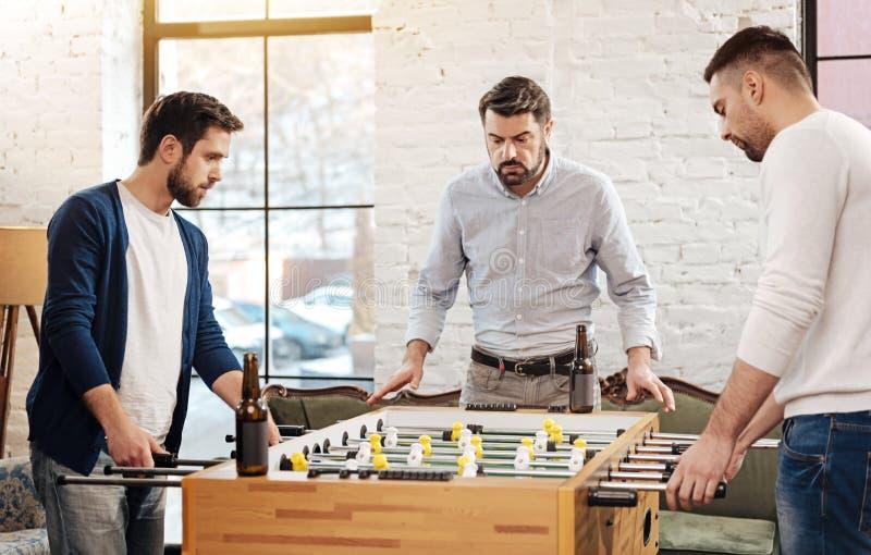 Hommes brutaux beaux jouant le football de table photo libre de droits