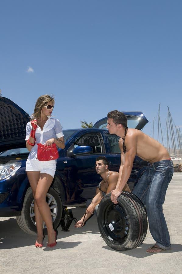 Hommes changeant une roue pour aider une femme image stock