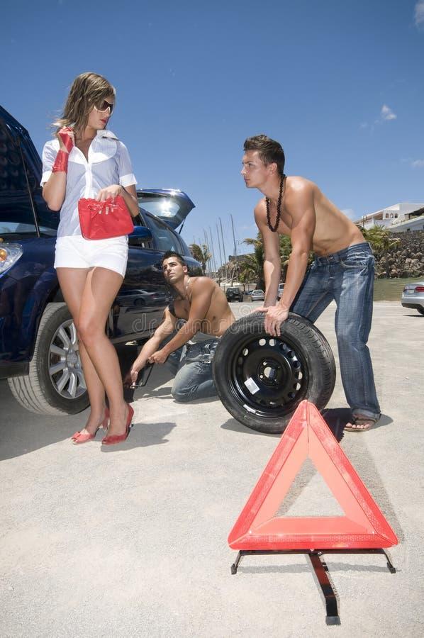 Hommes changeant une roue pour aider une femme image libre de droits
