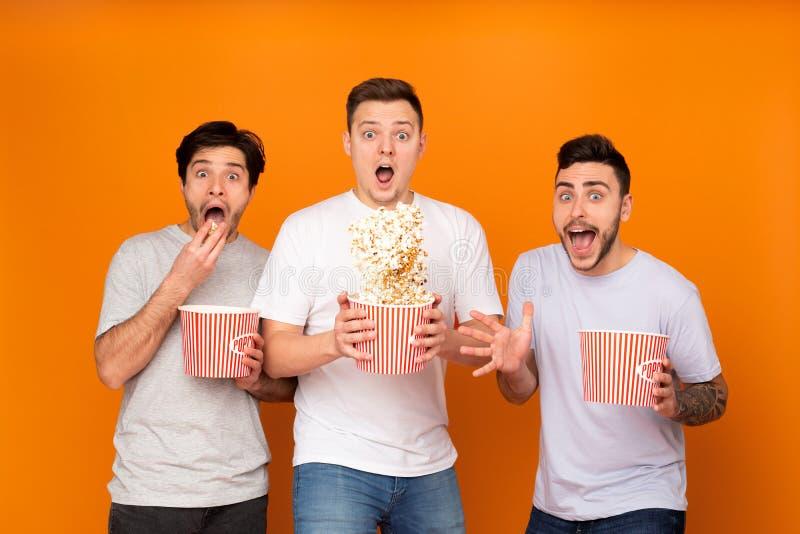 Hommes choqu?s mangeant du ma?s ?clat? et observant le film effrayant photo stock