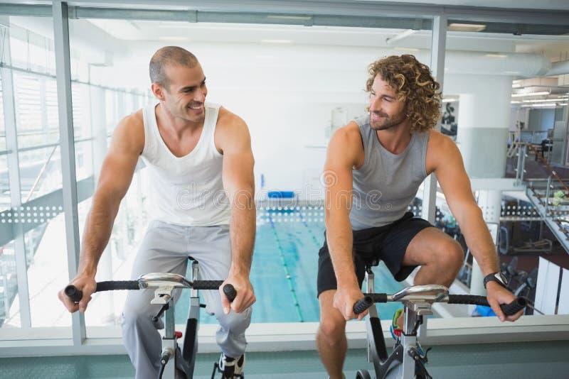 Hommes convenables travaillant aux vélos d'exercice au gymnase photographie stock libre de droits
