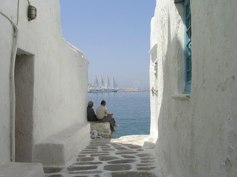Hommes détendant à la maison de bord de la mer, Mykonos, Grèce photographie stock libre de droits