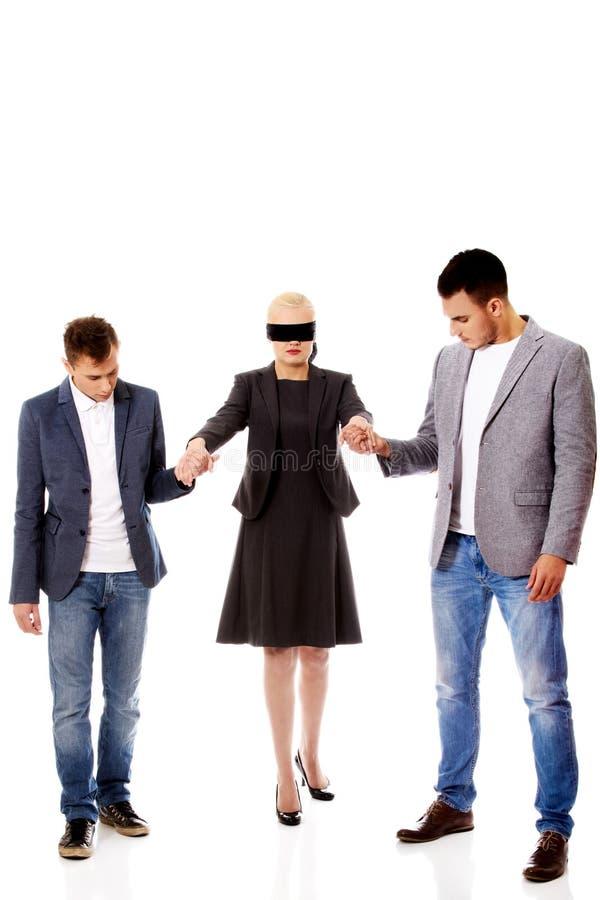 Hommes d'équipe-deux d'affaires aidant à la femme bandée les yeux image stock