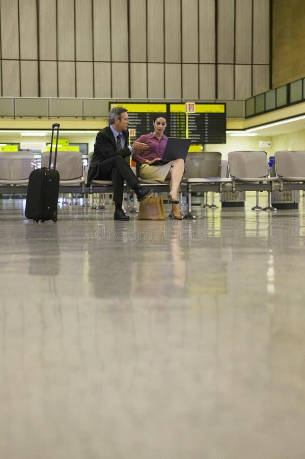 Hommes d'affaires à l'aide de l'ordinateur portable dans l'aéroport photo stock