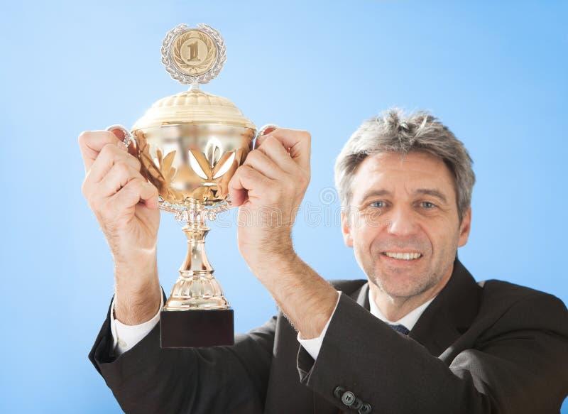 Hommes d'affaires aînés retenant un trophée images libres de droits