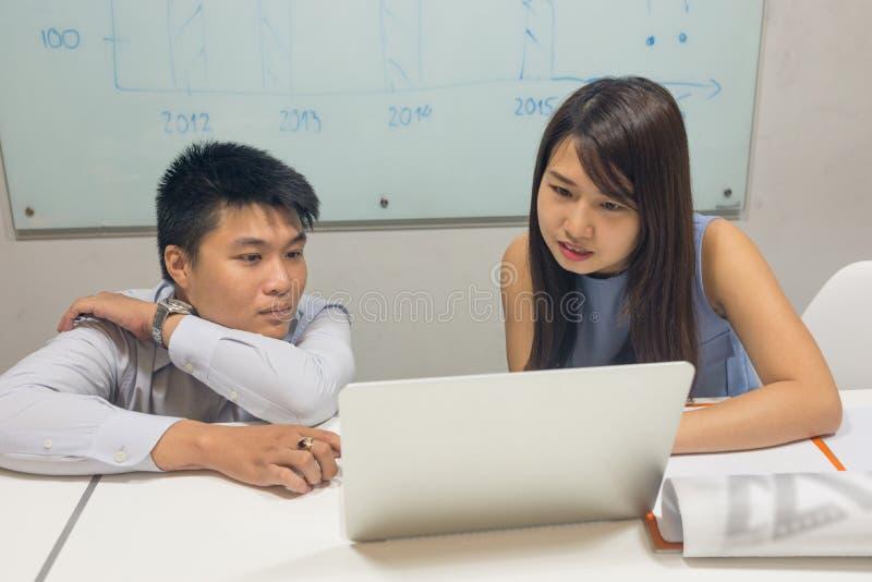 Hommes d'affaires analyser et discuter au sujet des données financières sur l'ordinateur portable images stock