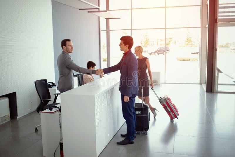 Hommes d'affaires arrivant à la réception d'hôtel photos libres de droits