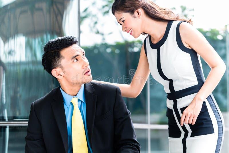 Hommes d'affaires asiatiques avec le problème de harcèlement sexuel images stock