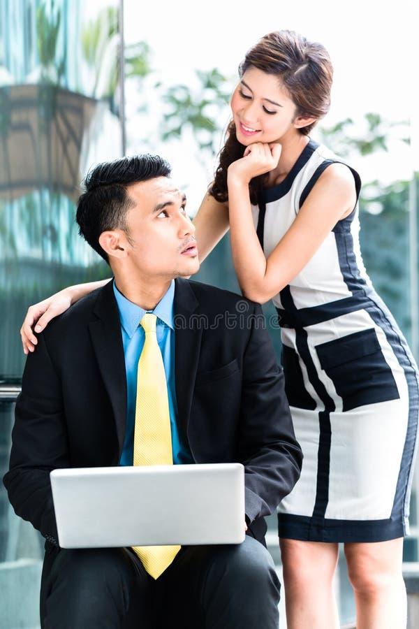 Hommes d'affaires asiatiques avec le problème de harcèlement sexuel photo stock