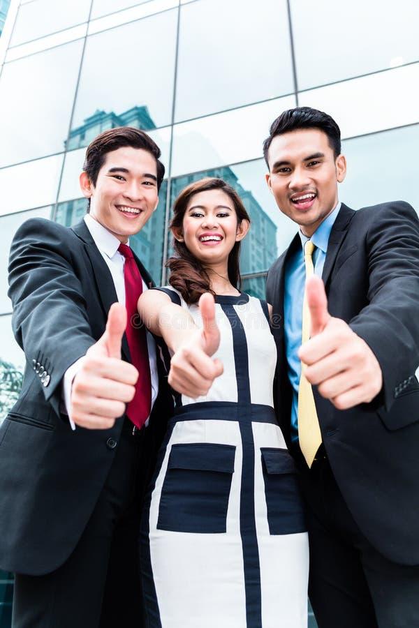 Hommes d'affaires asiatiques dehors devant le gratte-ciel photos stock