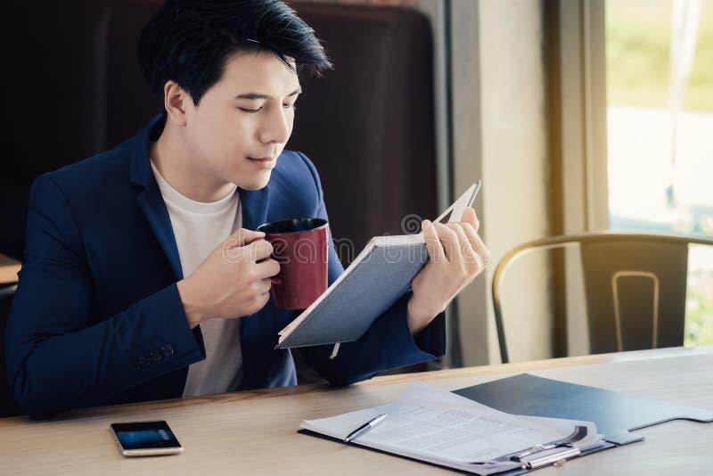 Hommes d'affaires asiatiques mangeant du café tout en travaillant pendant le matin photos libres de droits
