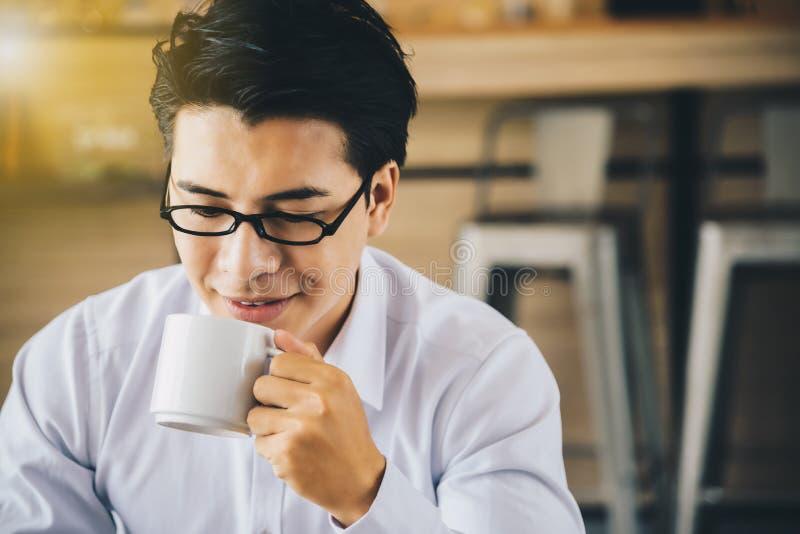 Hommes d'affaires asiatiques mangeant du café tout en travaillant pendant le matin photographie stock