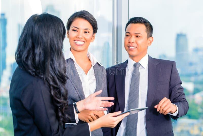 Hommes d'affaires asiatiques se tenant dans le bureau photo stock