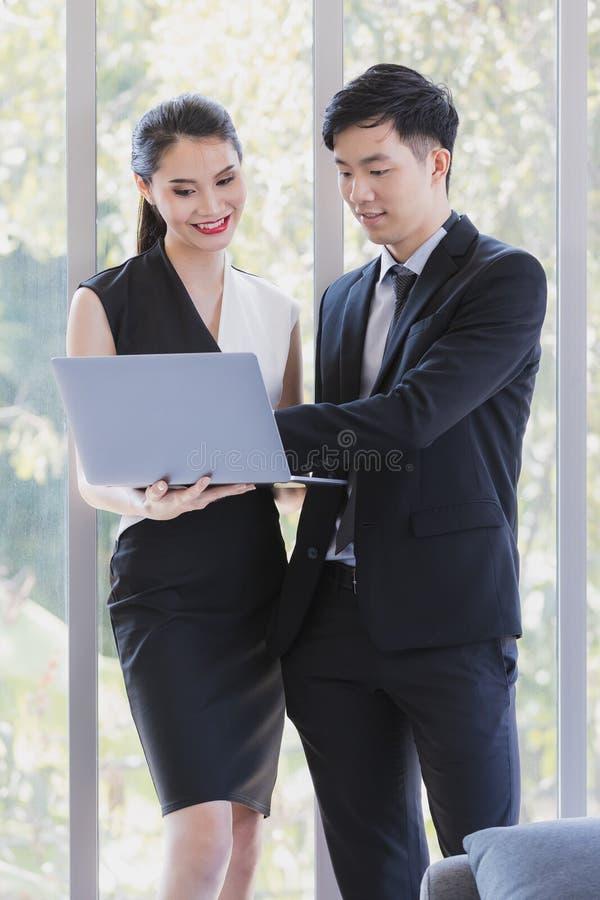 Hommes d'affaires asiatiques se tenant dans le bureau photographie stock