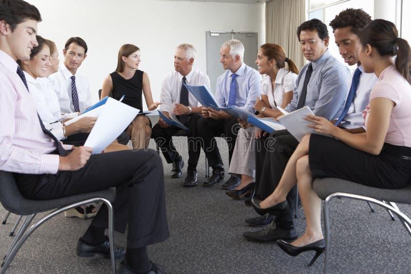 Hommes d'affaires assis en cercle lors du séminaire de société images stock