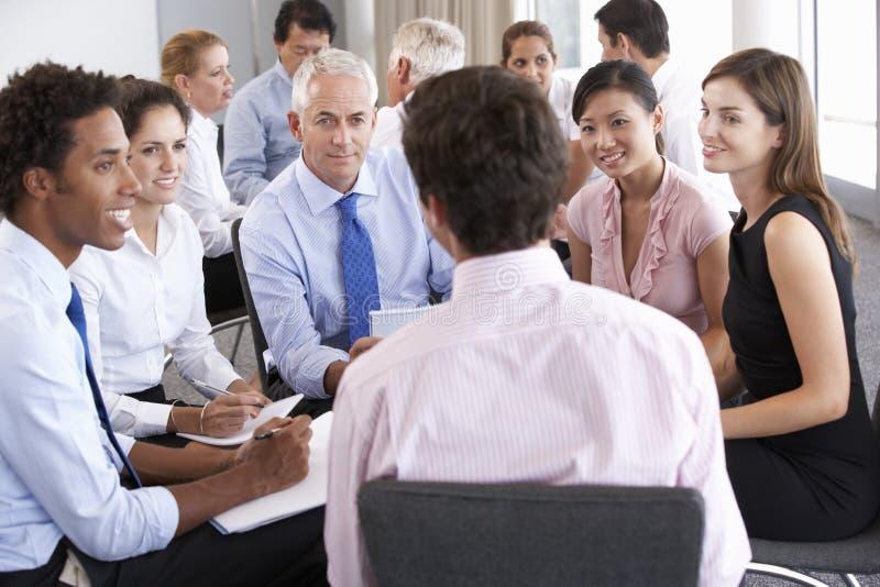 Hommes d'affaires assis en cercle lors du séminaire de société photos stock