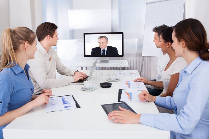 Hommes d'affaires assistant à la vidéoconférence image stock