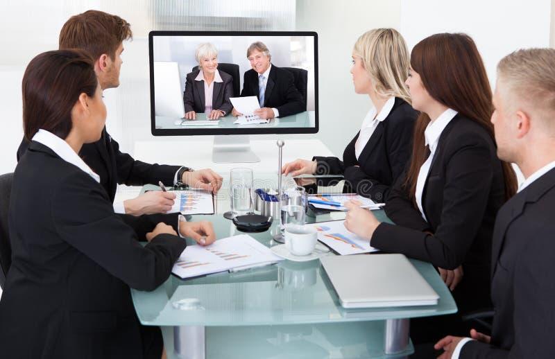 Hommes d'affaires assistant à la vidéoconférence images libres de droits