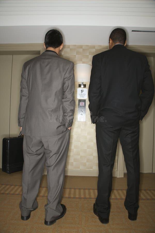 Hommes d'affaires attendant l'ascenseur photos libres de droits