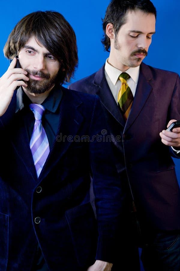 Hommes d'affaires avec des portables photographie stock