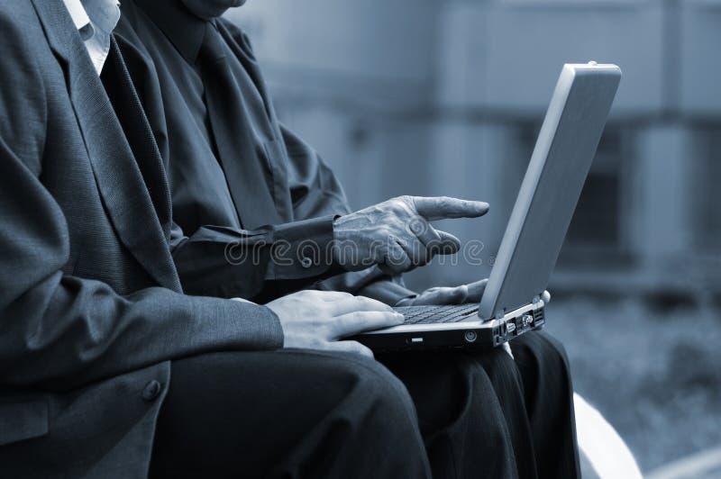 Hommes d'affaires avec l'ordinateur portatif photographie stock libre de droits