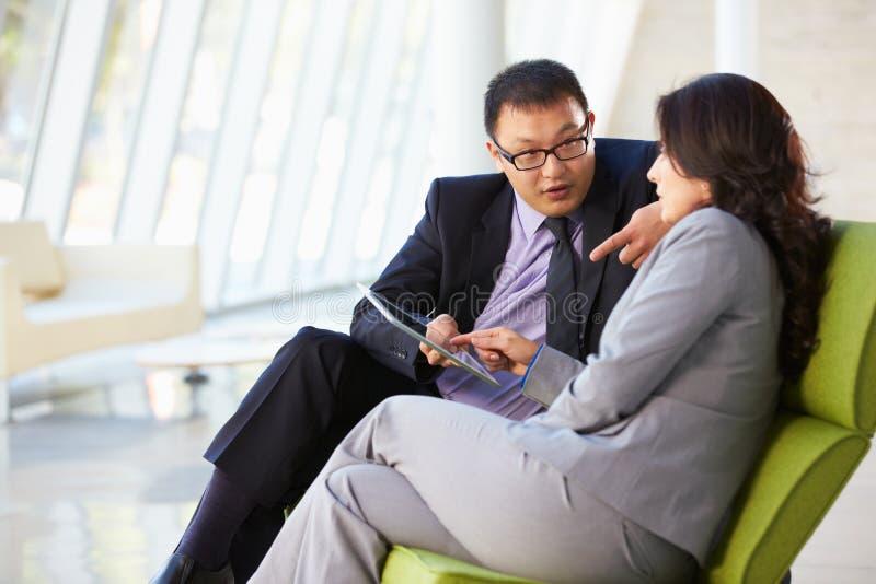 Hommes d'affaires avec la tablette de Digitals se reposant dans le bureau moderne photographie stock