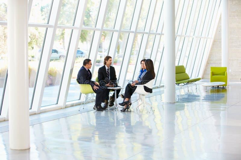 Hommes d'affaires ayant le contact dans le bureau moderne photos libres de droits