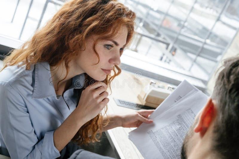 Hommes d'affaires ayant le déjeuner d'affaires à la femme s'asseyante de restaurant avec le document regardant l'homme songeur photos libres de droits