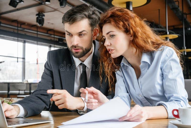 Hommes d'affaires ayant le déjeuner d'affaires à travailler se reposant de restaurant en ligne sur l'ordinateur portable photos stock