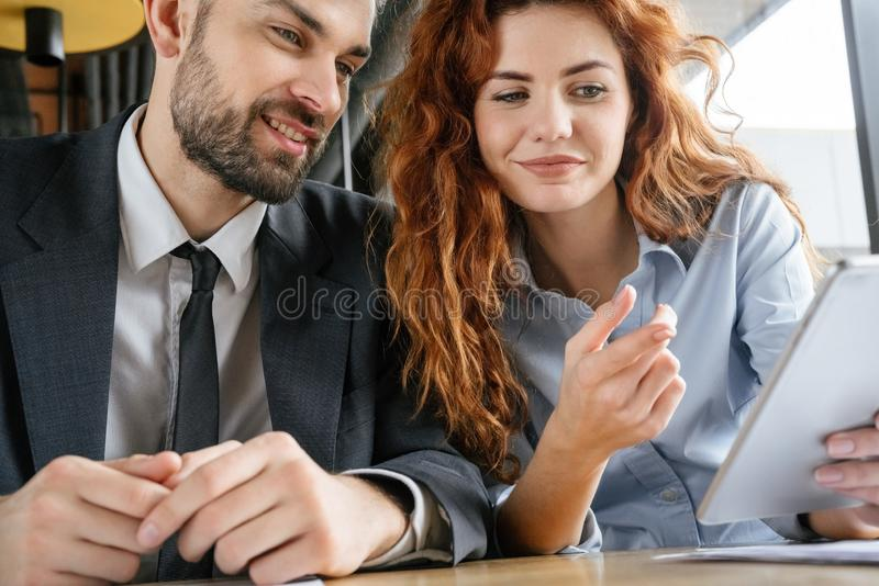 Hommes d'affaires ayant le déjeuner d'affaires au restaurant se reposant regardant le sourire numérique de comprimé images libres de droits