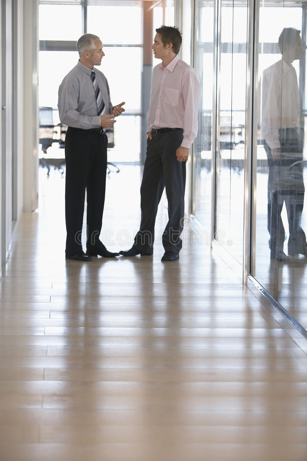 Hommes d'affaires ayant une discussion dans le couloir photos stock