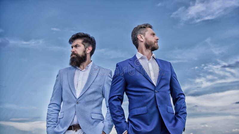 Hommes d'affaires barbus posant avec confiance Perfectionnez dans chaque d?tail Les hommes d'affaires tiennent le fond de ciel bl photographie stock