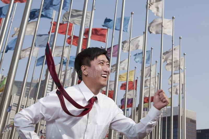 Hommes d'affaires courant et souriant avec des mâts de drapeau à l'arrière-plan. photos libres de droits
